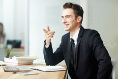 Handsome Entrepreneur with Toothy Smile. Cheerful young entrepreneur with toothy smile pointing at something while sitting in front of modern laptop at office Royalty Free Stock Photos