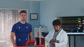 Handsome ethlete being tested and monitored by multiracial doctor during treadmill test in lab. EKG data are showed on big display in background stock video footage