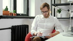 Handsome european boy working on project at modern office desk 20s 4k.  stock footage