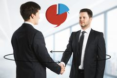Communication and team concept. Handsome european businessman shaking hands in blurry office interior with business pie chart and arrows. Communication and team Royalty Free Stock Photos