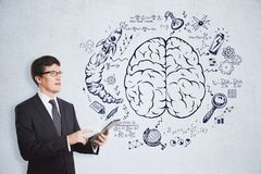 Brainstorming, success and management concept. Handsome european businessman using tablet on concrete wall background with business brain sketch. Brainstorming Stock Image