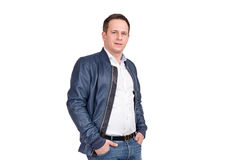 Handsome european man in white shirt, blue jeans and blue leather jacket. Holding hands in pockets while standing against white ba Royalty Free Stock Images