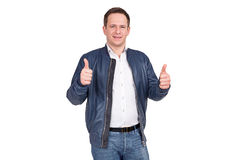 Handsome european man in white shirt, blue jeans and blue leather jacket holds his thumbs up. Royalty Free Stock Photos