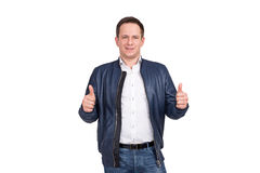 Handsome european man in white shirt, blue jeans and blue leather jacket holds his thumbs up. Stock Photography