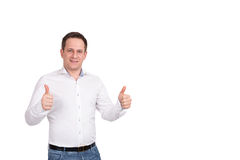 Handsome european man in white shirt and blue jeans holds his thumbs up Royalty Free Stock Image