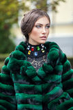 Handsome european model in a green fur coat Royalty Free Stock Images