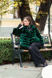 Handsome european model in a green fur coat  posing on a bench. Stock Photo