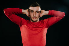 Handsome European sportsman wearing red sportswear and posing after hard exercise on dark background. Sporty man stretching with h. Caucasian sportsman wearing Royalty Free Stock Image