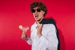 Handsome excited man in white shirt and jacket holding cocktail Stock Photos