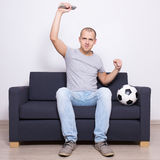 Handsome excited soccer fan watching game on television. Young handsome excited soccer fan watching game on television Stock Photography