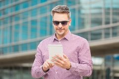 Handsome executive holding and looking at digital tablet device outdoors. stock photography