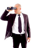 Handsome executive looking through binocular. Against white background Stock Photo