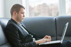 Handsome Executive Typing at Laptop Seriously Stock Photography
