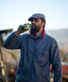Handsome farmer drinking beer Royalty Free Stock Photos