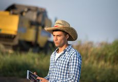 Farmer with combine harvester in field Stock Photo