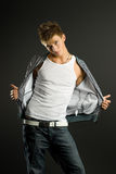 Handsome fashion boy. Handsome fashionable guy in white t-shirt and jeans posing in studio royalty free stock photo