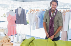 Handsome fashion designer cutting textile Stock Photography