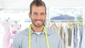 Handsome fashion designer holding a scissors smiling at camera stock video
