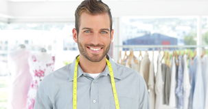 Handsome fashion designer holding a scissors smiling at camera stock video