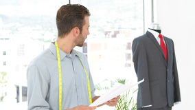 Handsome fashion designer looking at sketches and suit on mannequin stock video footage
