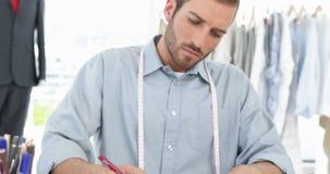 Handsome fashion designer sketching at his desk stock video