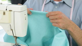 Handsome fashion designer using sewing machine stock footage