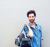 Handsome fashion man with beard holding travel bag Royalty Free Stock Photo
