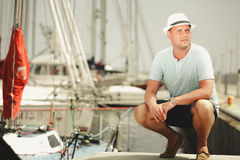 Handsome fashion man on pier in port with yachts. Stock Photography