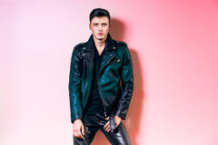 Handsome fashion man portrait, beautiful male model wear black leather jacket, pant and t-shirt posing near wall. Handsome fashion man portrait, beautiful male Stock Photography