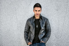 Handsome fashion man posing near the wall wearing grey leather coat, black t-shirt Stock Photo