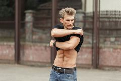 Handsome fashion model a man with a naked torso shoots a T-shirt. On the street Royalty Free Stock Images