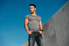 Handsome fashion model man posing outdoors wearing grey t-shirt and jeans. Handsome bearded fashion model man posing outdoors wearing grey t-shirt and jeans royalty free stock photo