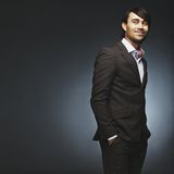 Handsome fashion model posing on black background. Attractive young man wearing suit standing with his hands in pocket looking over shoulder. Handsome male stock image