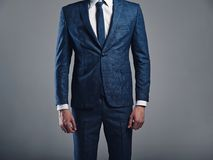 Handsome fashion stylish  businessman model dressed in elegant blue suit posing on gray Stock Photography