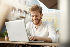 Handsome fashionable european male freelancer with trendy hair and beard sits outside in sunny weather, working on his Stock Photos