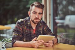 A handsome fashionable male freelancer with stylish haircut and beard, wearing fleece shirt, working on a tablet. Computer inside a cafeteria Stock Photos