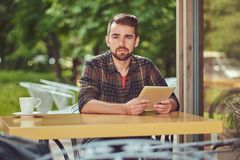 A handsome fashionable male freelancer with stylish haircut and beard, wearing fleece shirt, working on a tablet. Computer inside a cafeteria Stock Image