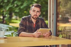 A handsome fashionable male freelancer with stylish haircut and beard, wearing fleece shirt, working on a tablet. Computer inside a cafeteria Stock Photography