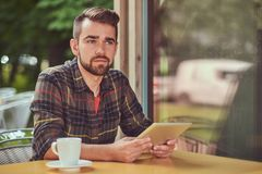 A handsome fashionable male freelancer with stylish haircut and beard, wearing fleece shirt, working on a tablet. Computer inside a cafeteria Royalty Free Stock Photos