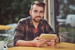 A handsome fashionable male freelancer with stylish haircut and beard, wearing fleece shirt, working on a tablet. A smiling handsome fashionable male freelancer Stock Photography