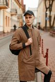 Handsome fashionable man in a spring stylish coat with a black. Cap with a bag on his shoulder posing on the street Royalty Free Stock Photography