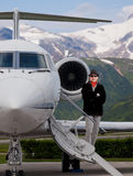 Handsome fashionable man on the steps of a private jet stock photography