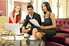 Handsome fashionable man with two charming women in a business meeting Royalty Free Stock Photography