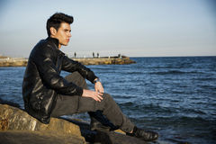 Handsome fashionable young man sitting at sea or Stock Images
