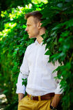 Handsome fashionable young man standing in the leaves of a wild Royalty Free Stock Photography