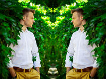 Handsome fashionable young man standing in the leaves of a wild Royalty Free Stock Photos