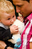 Handsome father with baby. Side portrait of handsome young father with baby son and toy Royalty Free Stock Photography