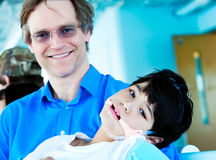 Handsome father in forties holding disabled son in arms Royalty Free Stock Photos