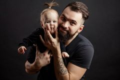 Young athletic father with adorable baby on black background royalty free stock photography