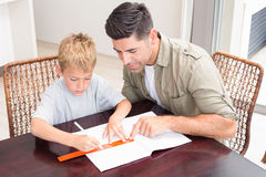 Handsome father helping son with homework at table Royalty Free Stock Images
